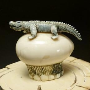 Krokodil auf Ei aus fossilem Walrosszahn